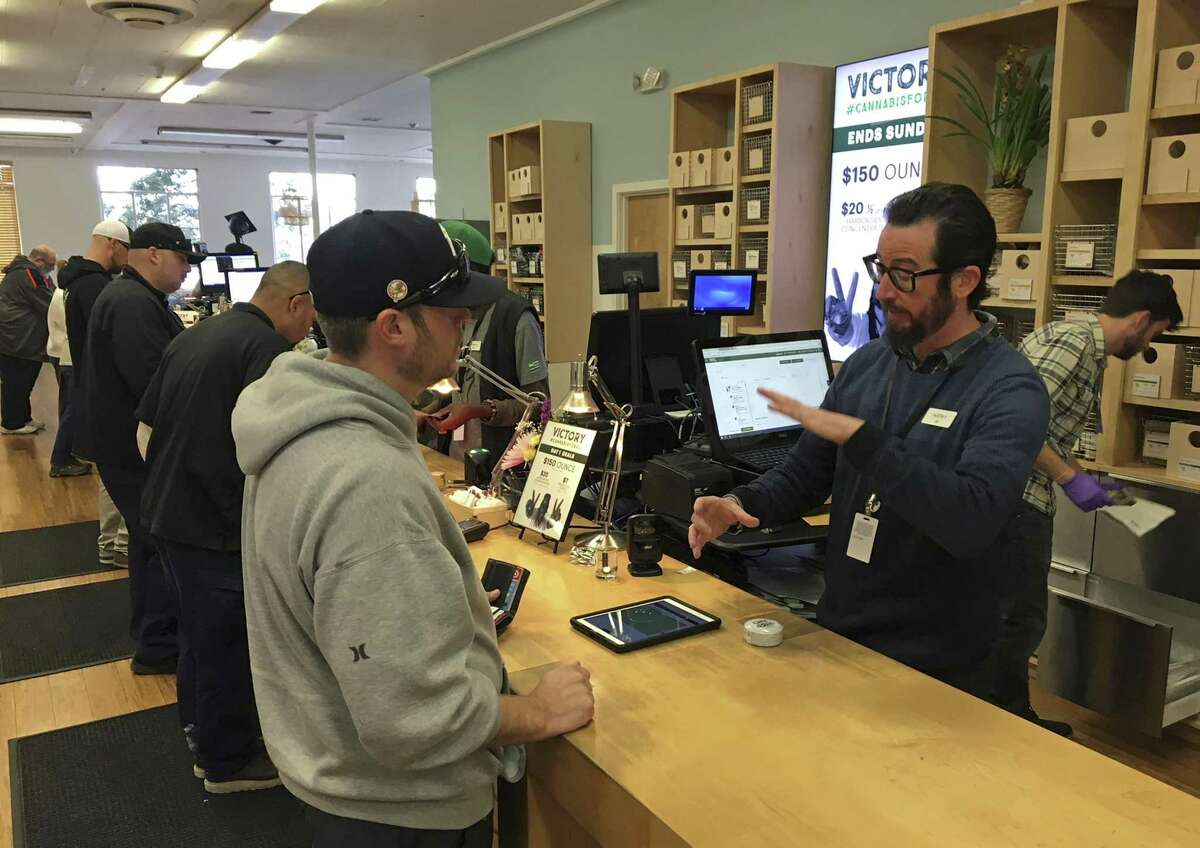 Budtender Austin Pitts, right, assists a customer inside the Harborside cannabis dispensary Thursday, Jan. 4, 2018, in Oakland, Calif. Attorney General Jeff Sessions has rescinded an Obama-era policy that paved the way for legalized marijuana to flourish in states across the country, creating new confusion about enforcement and use just three days after a new legalization law went into effect in California.
