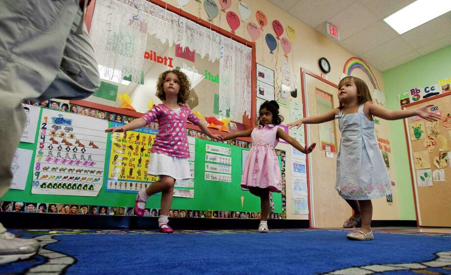 """Instructor Sati Babitzke demonstrates the """"flying flamingo"""" position  with Hannah Burrows, 5, Shyra Alli, 5 and Hannah Prince, 4., from left, as they do their daily yoga at the prestigious Goddard school Wednesday June 17, 2009 in Friendswood. Photo: Bob Levey / Freelance"""