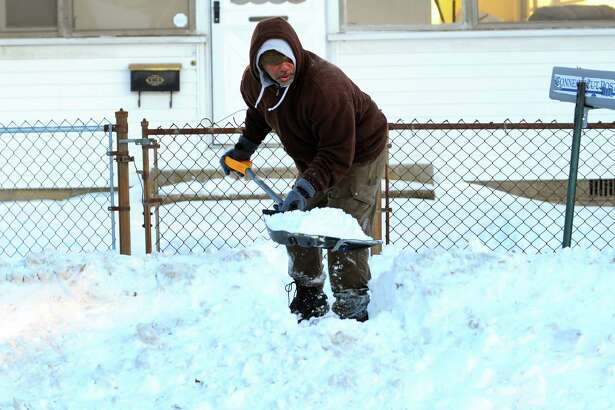 Ronald Bruce cleans up at a neighbor's house on Sylvan Ave in Bridgeport, Conn., on Friday Jan. 5, 2018. In the wake from Thursday's snow storm, extremely cold temperatures have settled in the area with temperatures dipping as low as 5 degrees in the overnight hours.