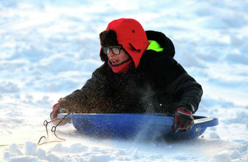 Families brave the frigid cold to do some sledding at Beardsley Park in Bridgeport, Conn., on Friday Jan. 5, 2018. In the wake from Thursday's nor'easter, extremely cold temperatures have settled in the area with temperatures dipping as low as 5 degrees in the overnight hours.