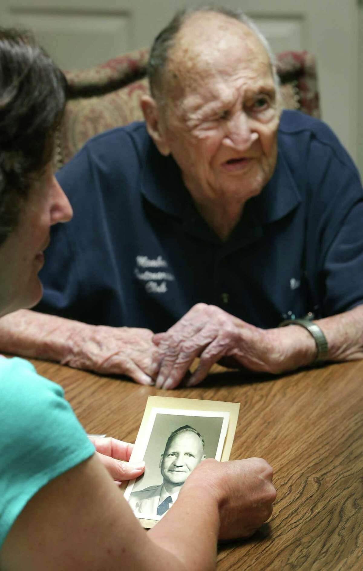 Eileen Friedeck, left, holds an old photo of her father Eugene Ruf, a veteran of World War II, as he is interviewed during the celebration of his 108th birthday on Wednesday, April 19, 2017, at Brookdale Senior Living Solutions.