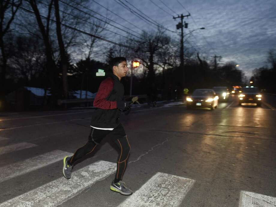 Distance runner Akash Molekudy, a junior, crosses East Putnam Avenue in the dark to finish up his training session at after-school indoor track practice at Greenwich High School in Greenwich, Conn. Wednesday, Jan. 3, 2018. Indoor track is one of the teams most affected by later start and dismissal times at GHS. Indoor track is a misnomer because students run outside, and because of the later dismissal time, now in the dark. Photo: Tyler Sizemore / Hearst Connecticut Media / Greenwich Time