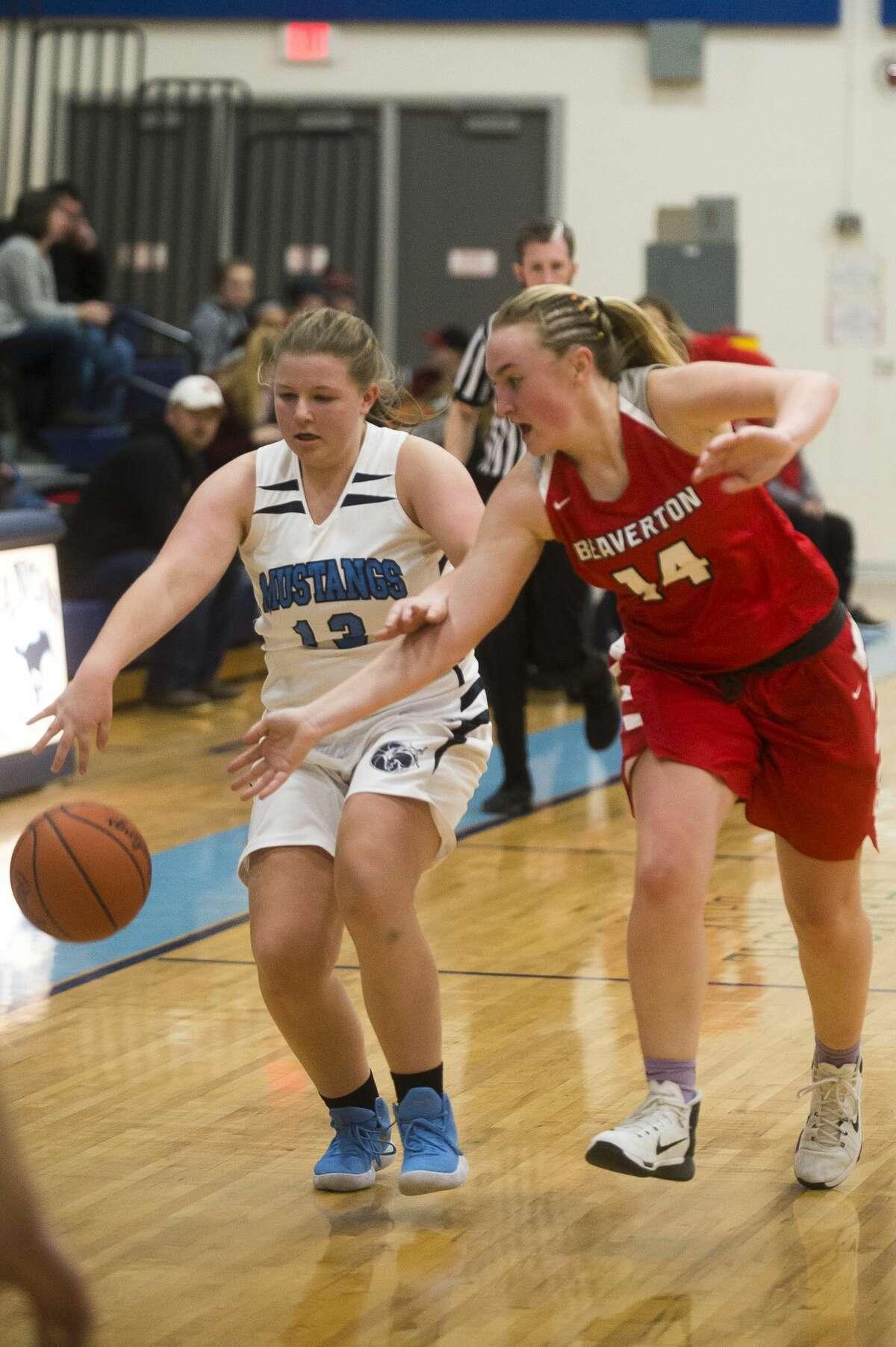 Meridian junior Karley Kent and Beaverton senior Ann-Marie Hicks fight for possession during their game on Friday, Jan. 5, 2018 at Meridian High School. (Katy Kildee/kkildee@mdn.net)