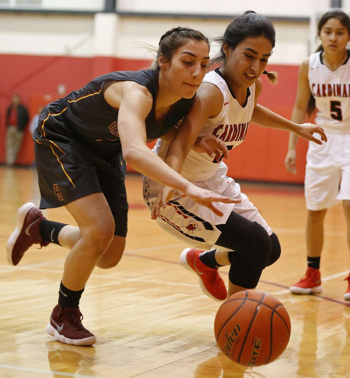 Harlandale's Fawzieh Saleh (left) and Southside's Alexis Tijerina chase after a loose ball during first half action held Friday Jan. 5, 2018 at Southside High School.