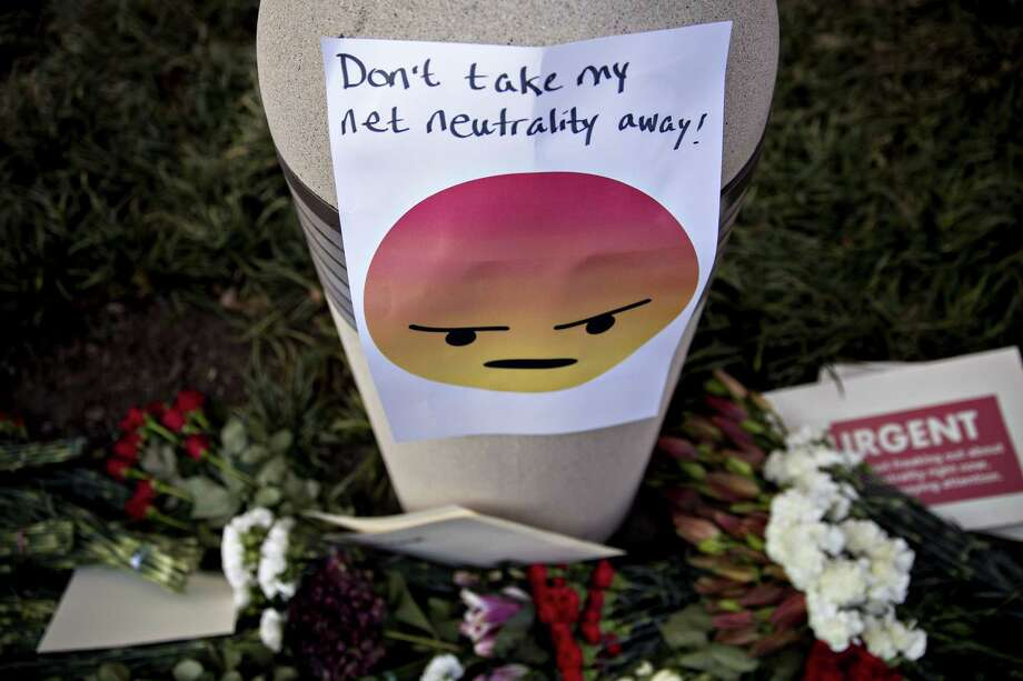 A sign against the roll- back of net neutrality rules is displayed near FCC headquarters.  Photo: Andrew Harrer / © 2017 Bloomberg Finance LP