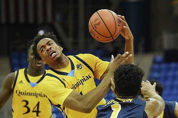 Quinnipiac senior guard Cameron Young is fouled by Canisius sophomore guard Malik Johnson for a loose ball, Friday, Jan. 5, 2018, at the TD Bank Sports Center in Hamden. Canisius won, 82-74.