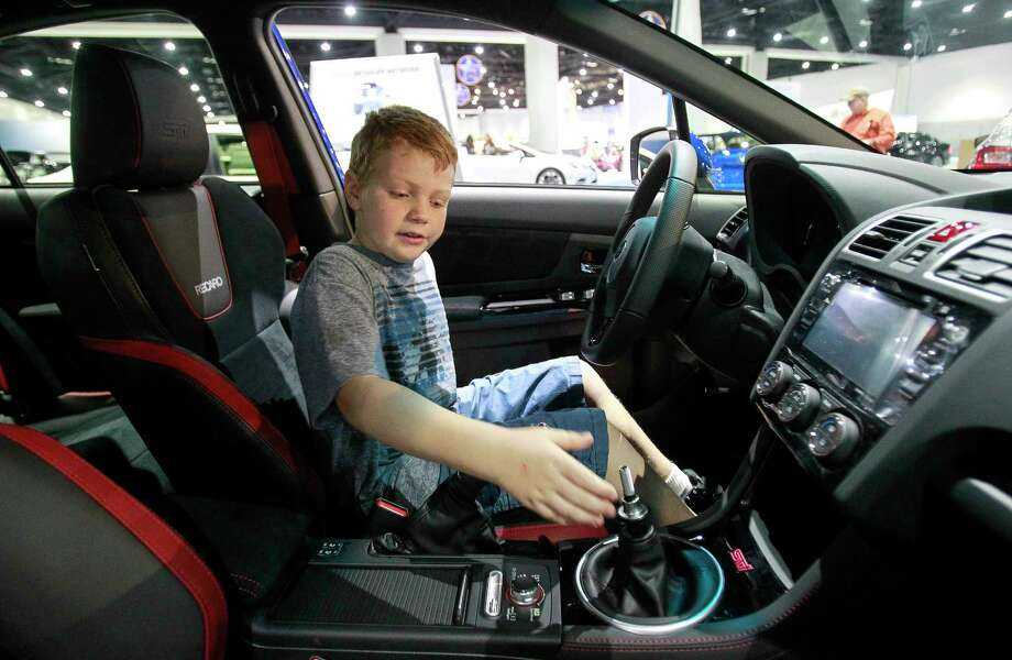 Spencer Willhite, 8, of Santee, Calif., checks out the manual transmission (the knob was removed to prevent theft) in a Subaru WRX at the recent San Diego International Auto Show.  Photo: Hayne Palmour IV, Staff Photographer / San Diego Union-Tribune