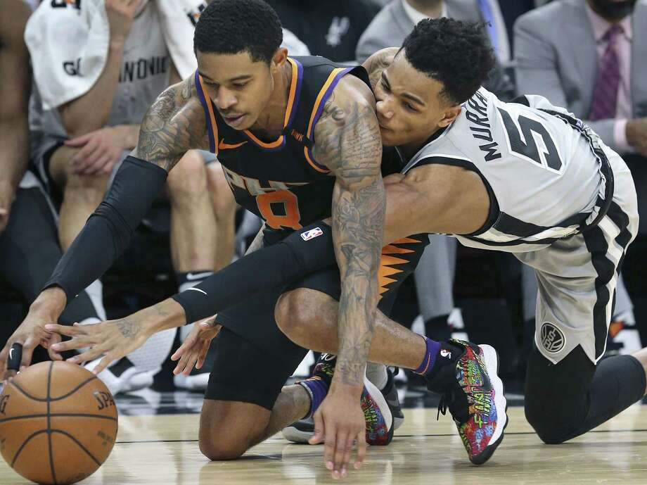 Dejounte Murray reaches under to get the ball loose from Tyler Ulis on the floor, causing a turnover as the Spurs host the Suns at the AT&T Center on January 5, 2018 Photo: Tom Reel, Staff / San Antonio Express-News / 2017 SAN ANTONIO EXPRESS-NEWS