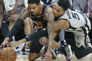 Dejounte Murray reaches under to get the ball loose from Tyler Ulis on the floor, causing a turnover as the Spurs host the Suns at the AT&T Center on January 5, 2018