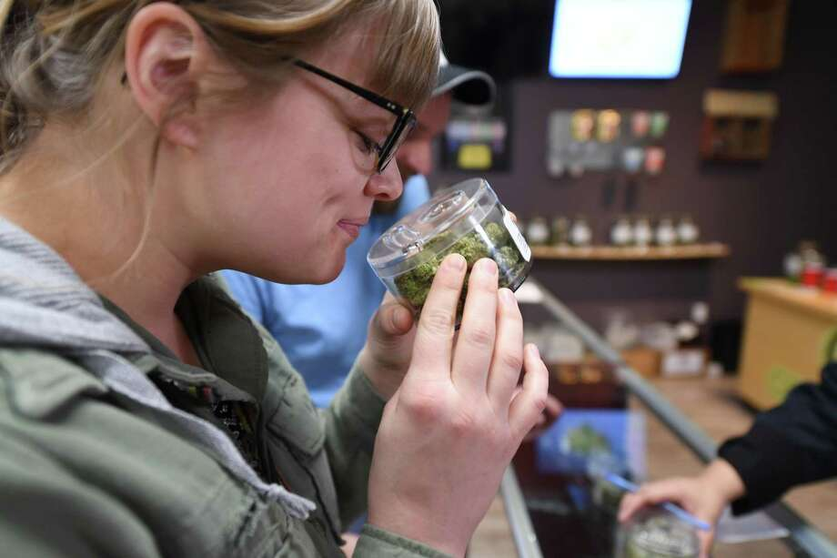 Tourist Laura Torgerson, visiting from Arizona, smells cannabis buds at the Green Pearl Organics dispensary on the first day of legal recreational marijuana sales in California, January 1, 2018 in Desert Hot Springs, California. / AFP PHOTO / Robyn BeckROBYN BECK/AFP/Getty Images Photo: ROBYN BECK, Contributor / AFP or licensors