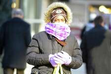 Shayna Bailey of Stamford bundles up from the cold weather as she walks home on Jan. 19, 2016. Area resident are preparing for a late-week snowstorm from the Mid-Atlantic to the Northeast.