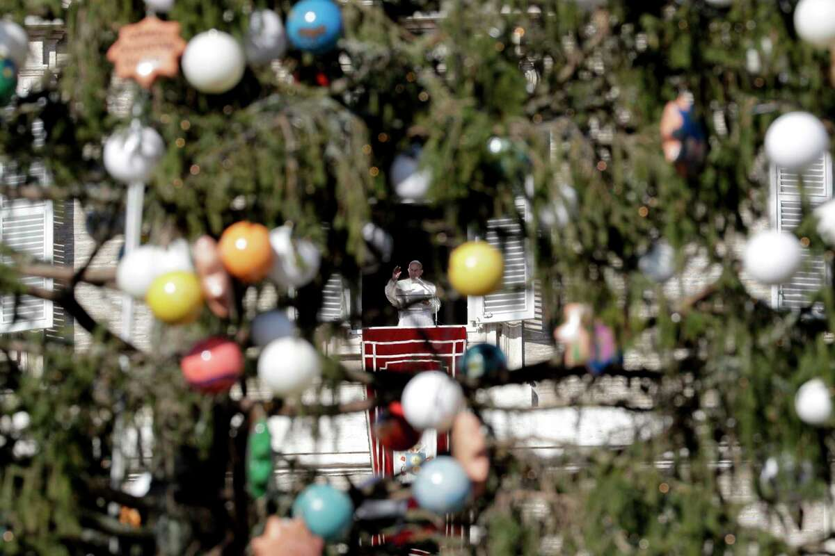 Pope Francis is seen through a decorated Christmas tree as he delivers his blessing as he recites the Angelus noon prayer from the window of his studio overlooking St. Peter's Square at the Vatican, Saturday, Jan. 6, 2018.