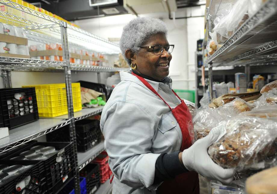 Anita Osborne, of Norwalk, stocks shelves with loaves of donated bread at Person-to-Person at 76 South Main St. in Norwalk on Wednesday, Nov. 22, 2017. The organization, with sites in Norwalk and Darien, handed out over 700 turkeys and 12,000 pounds of produce to those in need in preparation for the Thanksgiving holiday. Photo: Brian A. Pounds / Hearst Connecticut Media / Connecticut Post