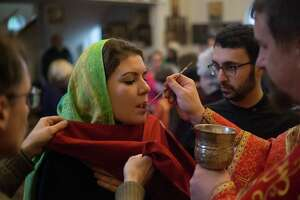Churchgoers take communion during the Russian Orthodox celebration of Theophany on Friday, Jan. 6, 2018 at St. Spiridon Orthodox Cathedral in Seattle.