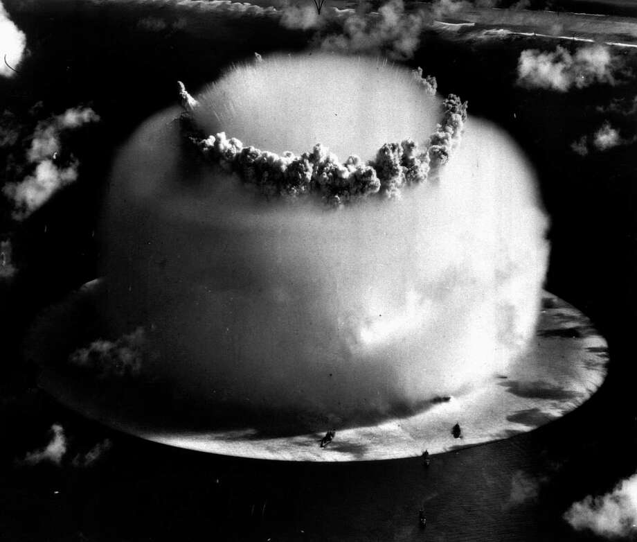 """A huge mushroom cloud rises above Bikini atoll in the Marshall Islands July 25, 1946 following an atomic test blast, part of the U.S. military's """"Operation Crossroads."""" The dark spots in foreground are ships that were placed near the blast site to test what an atom bomb would do to a fleet of warships. (AP Photo) / AP1946"""