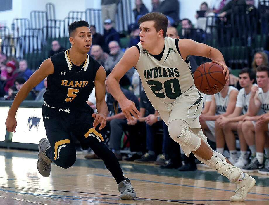 Guilford's Matt Donlan drives around Hand's KJ Richmond in a rivalry game, Saturday, Jan. 6, 2018, at the gymnasium at Guilford High School. Guilford won, 59-42. Photo: Catherine Avalone, Hearst Connecticut Media / New Haven Register
