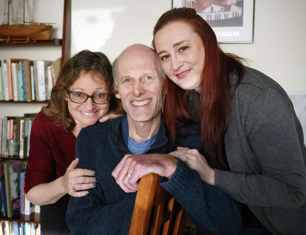 Dr. David A. Ross Russell, 57, diagnosed with metastatic pancreatic cancer, at home in East Haven with his wife Dorothy Goldberg, left, and their daughter, Bekka Ross Russell, of Branford, on Wednesday.