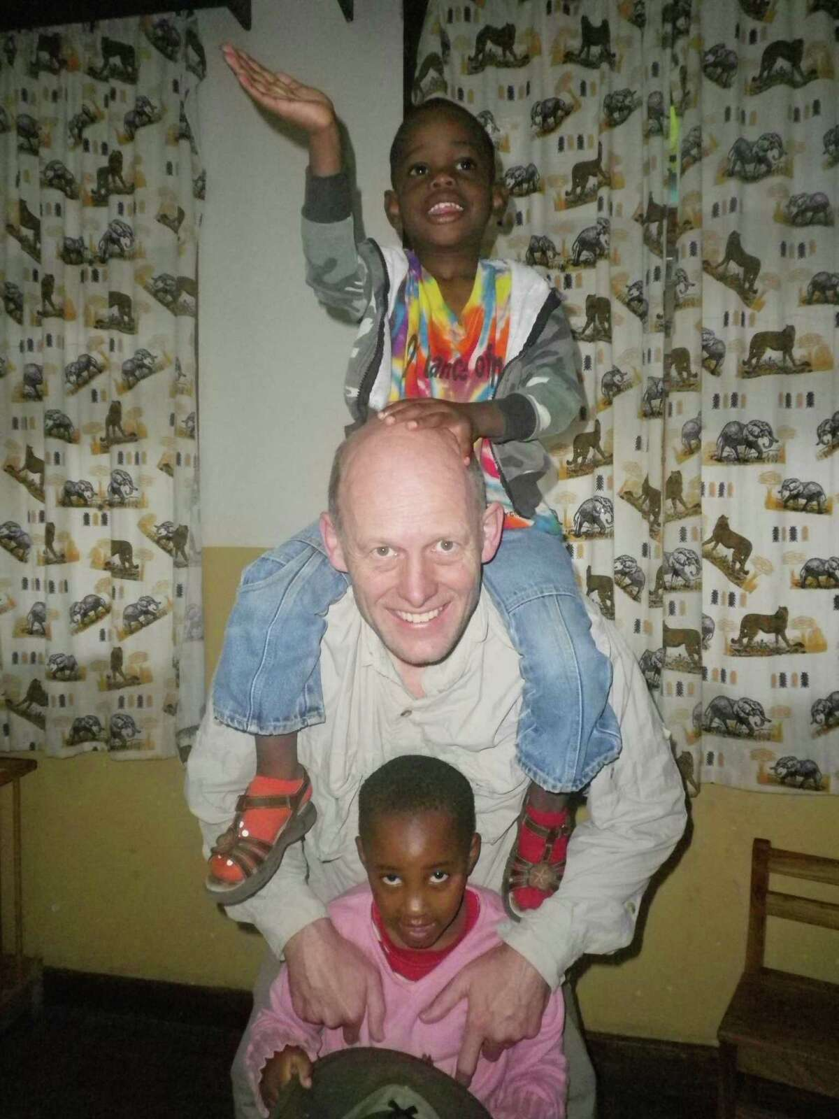 Dr. David Ross Russell plays with Stevie, on his shoulders, and Farajah at The Small Things orphanage in Nkoaranga, Tanzania.