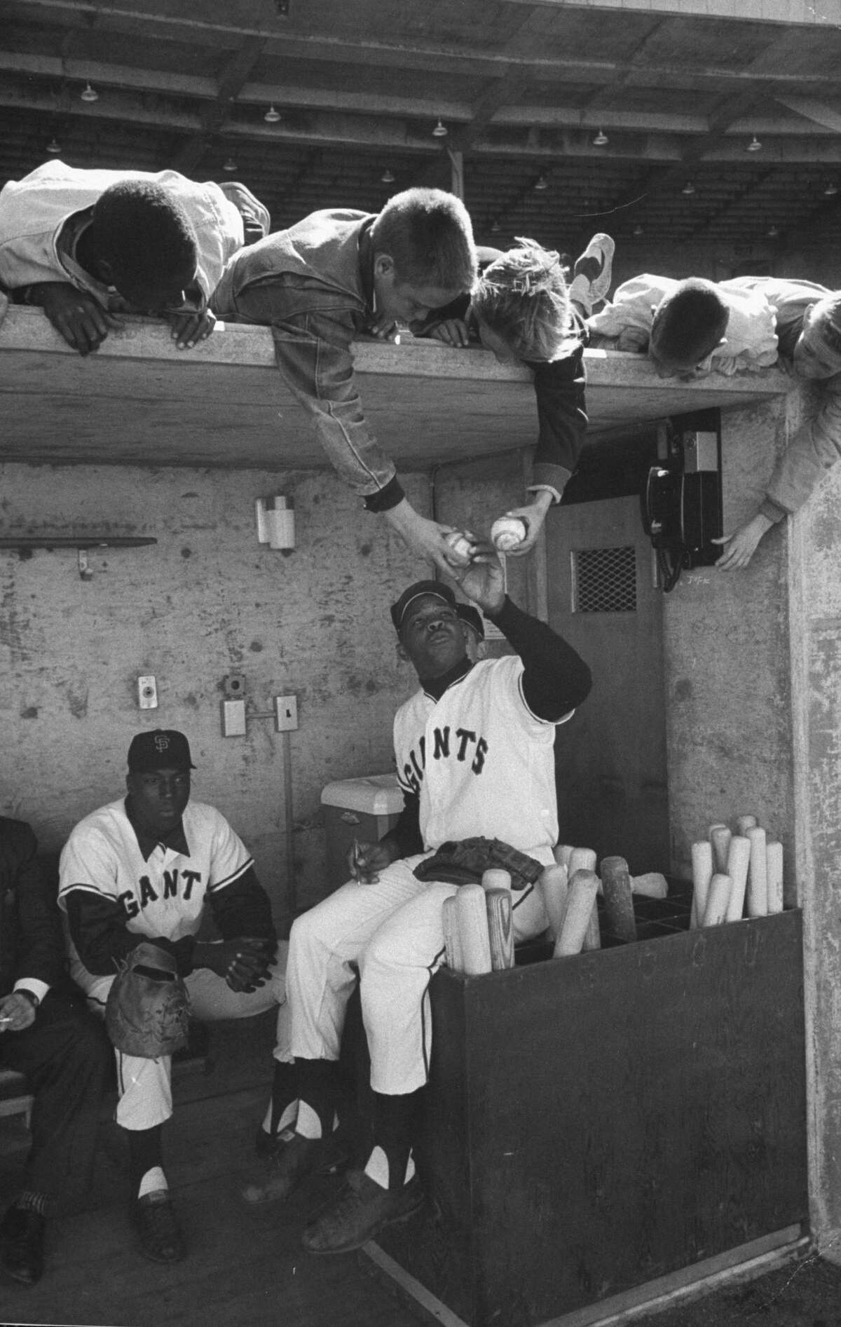 Giants baseball players Willie Mays (right) and Willie McCovey (left) sign autographs for fans while in dugout at Candlestick Park in San Francisco.