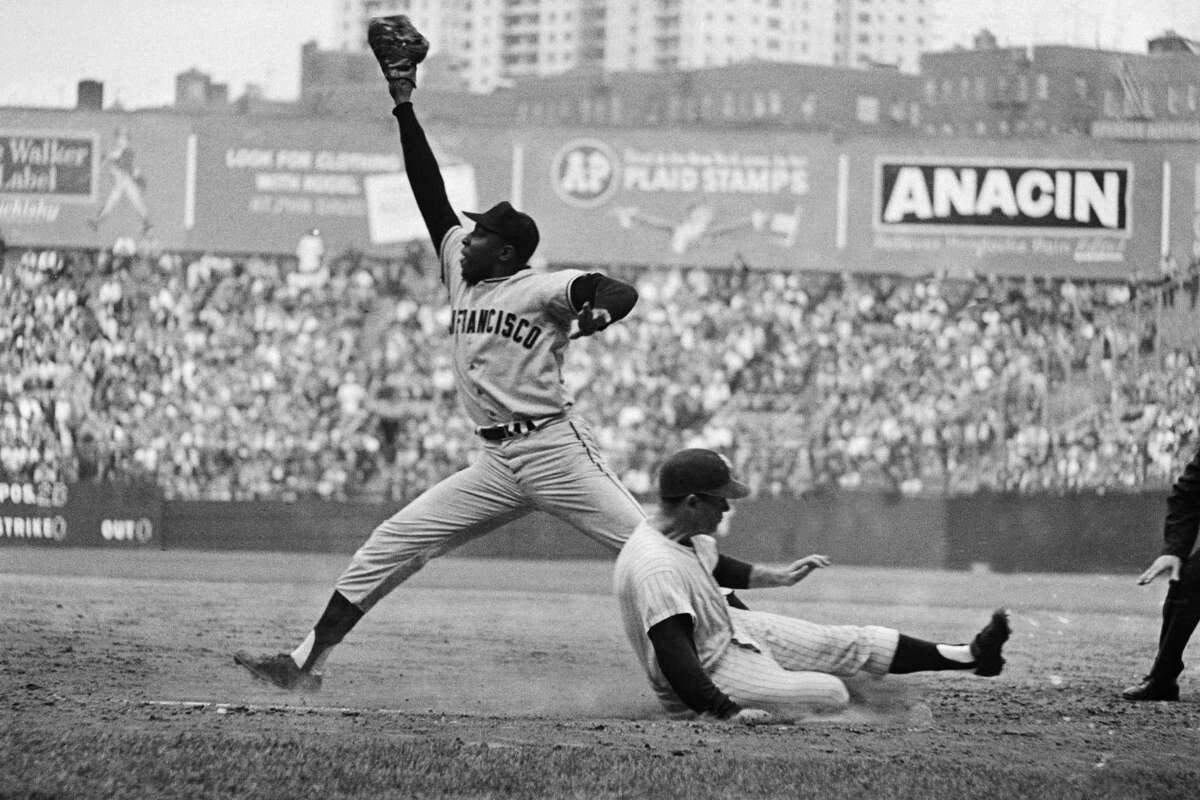 Bobby Richardson slides safely into first as Willie McCovey stretches for the late throw during game 5 of the 1962 World Series between the San Francisco Giants and New York Yankees. The Yankees defeated the Giants 4 games to 3.