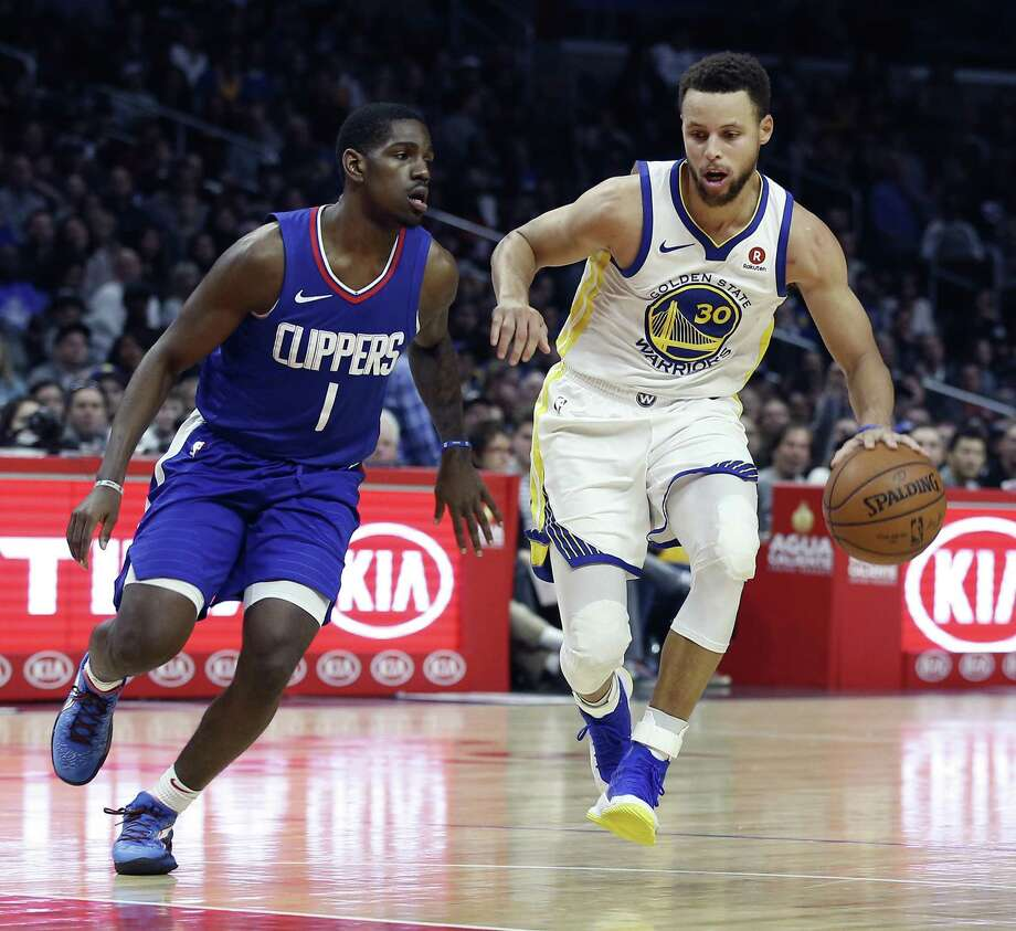 Golden State Warriors guard Stephen Curry, right, dribbles around Los Angeles Clippers guard Jawun Evans during the second half of an NBA basketball game in Los Angeles, Saturday, Jan. 6, 2018. Behind Curry's 45 points, the Warriors won 121-105. (AP Photo/Alex Gallardo) Photo: Alex Gallardo / AP / FR170211 AP