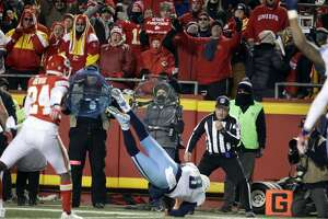 Tennessee Titans quarterback Marcus Mariota (8) leaps for a touchdown in front of Kansas City Chiefs defensive back Will Redmond (24) during the second half of an NFL wild-card playoff football game, in Kansas City, Mo., Saturday, Jan. 6, 2018. (AP Photo/Charlie Riedel)