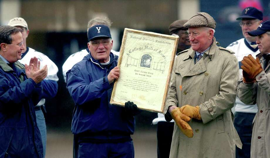 Carmen Cozza, center, shows off a plaque he received from the National Football Foundation College Hall of Fame during halftime of a 2002 game against Penn at Yale Bowl. At left is former Yale president Rick Levin. Photo: Hearst Connecticut Media File Photo