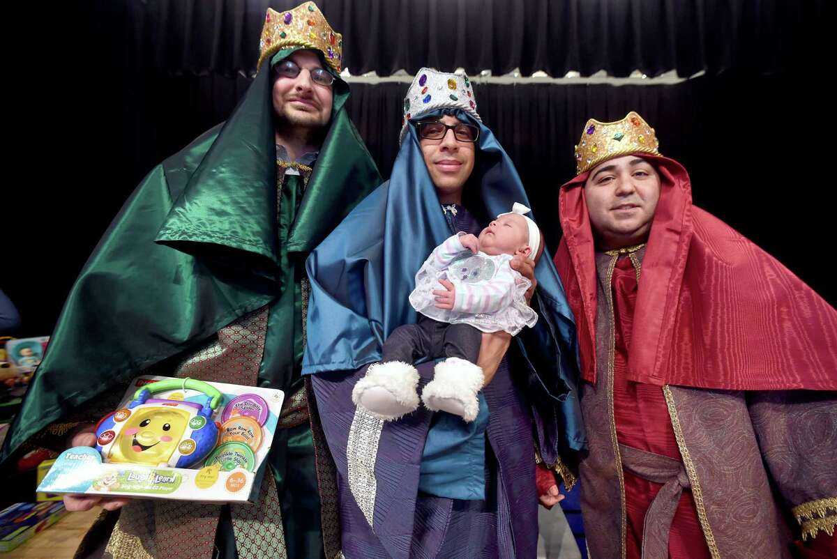 Left to right, State Rep. Al Paolillo, Jr., Jhonathan Rivera of Puerto Ricans United and Joe Rodriguez as the Three Kings pose for a photograph with one-month-old Lairalys Yainamar Bayron Marrero during a Three Kings Day event at the John C. Daniels Interdistrict Magnet School of International Communication in New Haven on Saturday. Lairalys' mother moved from Puerto Rico to East Haven in November after Hurricane Maria.