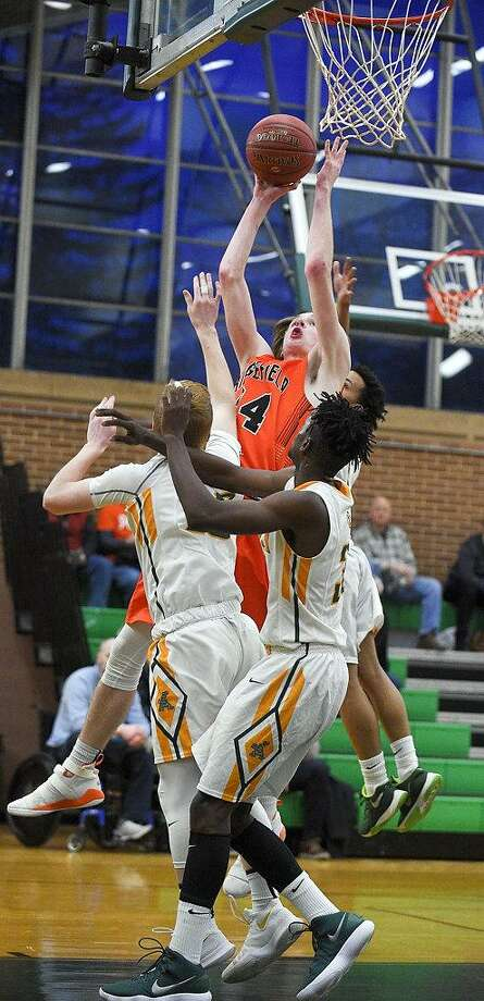 Trinity's Jack Soucy (10), Dimitry Moise (35) and Cameron Blake (3) contest the shot of Ridgefield's Brenden McNamara (34) in a FCIAC boys basketball game at Trinity Catholic High School's Walsh Court in Stamford, Conn. on Saturday, Jan. 6, 2018. Ridgefield defeated Trinity in overtime 64-63. Photo: Matthew Brown / Hearst Connecticut Media / Stamford Advocate