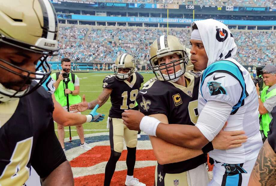 FILE - In this Sept. 24, 2017, file photo, Carolina Panthers' Cam Newton (1) and New Orleans Saints' Drew Brees (9) embrace before an NFL football game in Charlotte, N.C. Saints coach Sean Payton takes a small measure of comfort in New Orleans' regular-season sweep of Carolina. It means the Saints  play the Panthers (11-5) in the Superdome, where New Orleans hasn't lost a playoff game since 1992 and is 4-0 in the postseason under Payton. (AP Photo/Bob Leverone, File) Photo: Bob Leverone, FRE / FR170480 AP