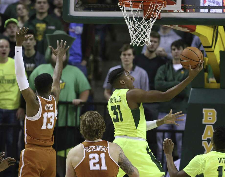 Baylor forward Terry Maston, right, scores past Texas guard Jase Febres, left, in the first half Saturday in Waco. Baylor won 69-60. Photo: Rod Aydelotte /Associated Press / Waco Tribune-Herald