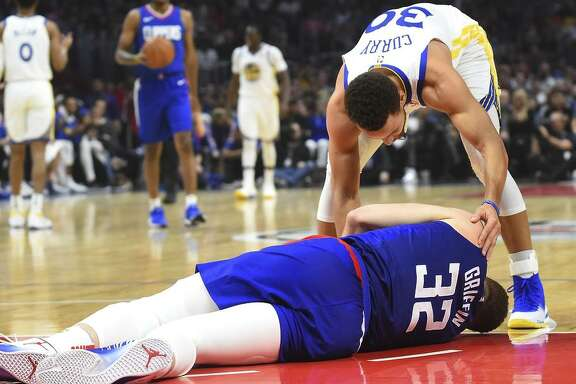 Stephen Curry checks on the Clippers' Blake Griffin, who suffered a concussion during Saturday's loss in Los Angeles.