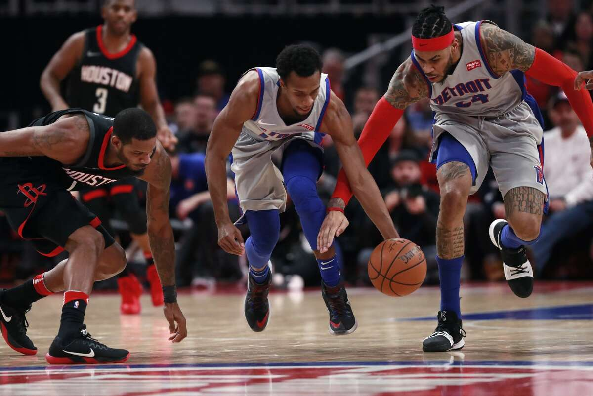 Houston Rockets forward Trevor Ariza, left, Detroit Pistons guard Ish Smith, center and Pistons forward Eric Moreland (24) chase the loose ball during the first half of an NBA basketball game, Saturday, Jan. 6, 2018, in Detroit. (AP Photo/Carlos Osorio)