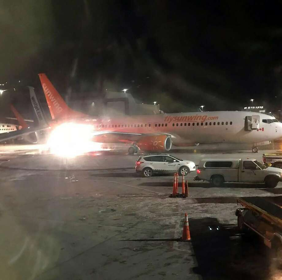 A picture obtained from the Facebook account of Connie Carson shows a Sunwing's airplene (front) colliding with a WestJet plane (L rear) on January 5, 2018, at Toronto's Pearson Airport. Both WestJet and Sunwing confirmed that their planes were involved in the collision. Video footage shared on social media appeared to show the tail of one aircraft aflame and spewing black smoke, and later images indicated that it was Sunwing's plane. Photo: CONNIE CARSON, AFP/Getty Images