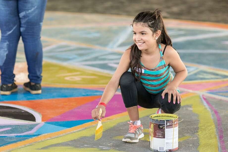 A child paints a mural in a Puerto Rican neighborhood that had been damaged by Hurricane Maria. A group from the Fairfield-based Save the Children recently worked with residents and leaders the neighborhood to design the mural. Photo: Gabriel González For The Save The Children / Contributed