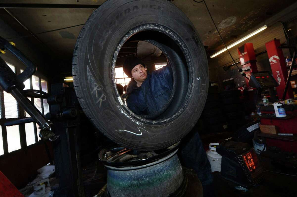 Employees at Currie's Tires for Less including Jorge Badella work on motor vehicle tires Friday, January 5, 2018, at the shop of West Ave. in Norwalk, Conn. Severe cold weather effects vehicles adversely and in particular wheels and tires.