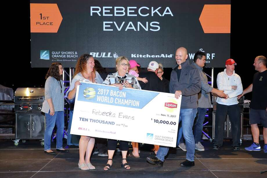 Rebecka Evans of Pearland, center, holds the $10,000 check she won in the bacon category of the  World Food Championships held in Orange Beach, Alabama. She hopes to win the $100,000 top prize at the 2018 World Food Championship in April. Photo: Courtland William Richards / Copyright 2017 Courtland William Richards
