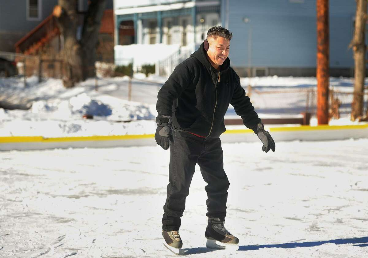 Below, Jaime Fonseca, of Ansonia, tries ice skating during the grand opening of the new winter playground at Linett Park on Crowley Street in Ansonia, Conn. on Sunday, January 7, 2018.