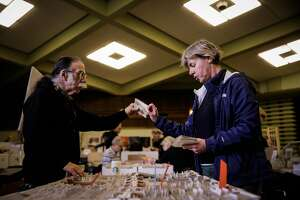 Alice Van Ommeren (right) hands Edward Henry a vintage postcard as she looks around at the Vintage Paper Fair in San Francisco, Calif., on Sunday, Jan. 7, 2018.