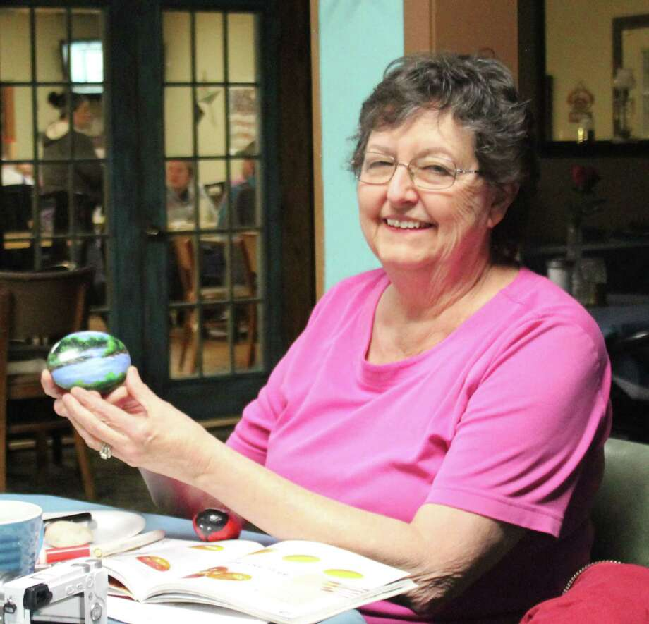 Linda Deeter displays a painted rock she created, which shows a scene from Double Lakes. Photo: Jacob McAdams