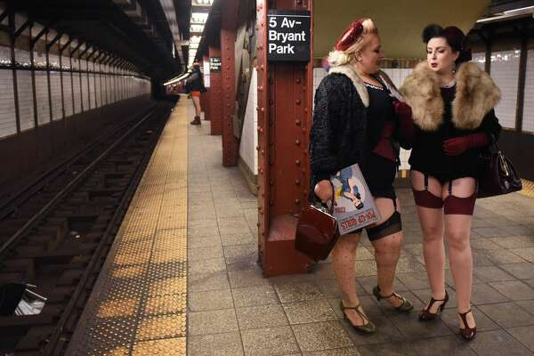 """Participants in the 17th Annual """"No Pants Subway Ride"""" wait for a New York City subway train on January 7, 2018 in New York.  The """"No Pants Subway Ride"""" is an annual event started in 2002 by Improv Everywhere in New York, the goal of which is for riders ride the subway train dressed in normal winter clothes without pants while keeping a straight face. / AFP PHOTO / TIMOTHY A. CLARY        (Photo credit should read TIMOTHY A. CLARY/AFP/Getty Images)"""