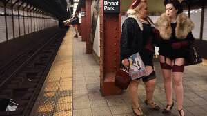 "Participants in the 17th Annual ""No Pants Subway Ride"" wait for a New York City subway train on January 7, 2018 in New York.  The ""No Pants Subway Ride"" is an annual event started in 2002 by Improv Everywhere in New York, the goal of which is for riders ride the subway train dressed in normal winter clothes without pants while keeping a straight face. / AFP PHOTO / TIMOTHY A. CLARY        (Photo credit should read TIMOTHY A. CLARY/AFP/Getty Images)"