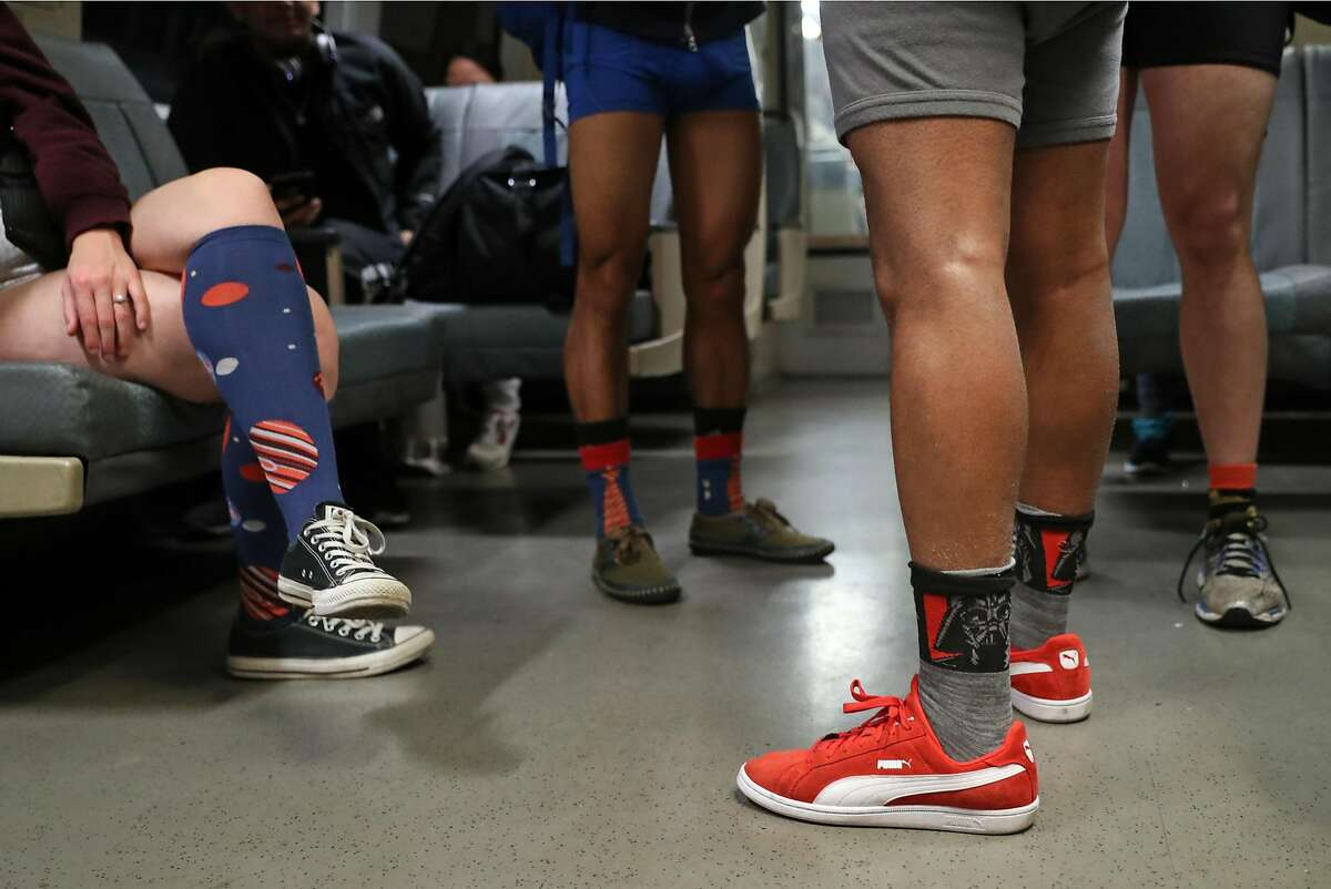 Event organizer Vivek Ramachandran (red shoes) joins others on BART during No Pants! Subway Ride 2018 in San Francisco, Calif., on Sunday, January 7, 2018.