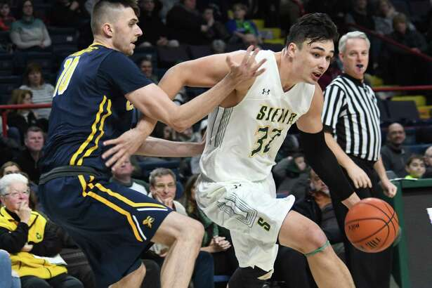 Siena forward Evan Fisher dribbles the ball past Canisius center Selvedin Planincic during an MAAC conference game on Sunday, Jan. 7, 2018 at the Times Union Center in Albany, N.Y. Siena held on for a 65-62 victory against Canisius. (Jenn March/Special to the Times Union)
