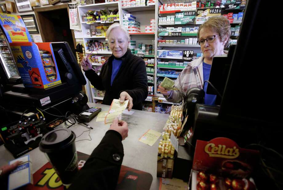 Cashiers Kathy Robinson, left, and Ethel Kroska, right, both of Merrimack, N.H., sell a lottery ticket Sunday, Jan. 7, 2018, to Diane Ackley, hand only below, at Reeds Ferry Market convenience store, in Merrimack. A lone Powerball ticket sold at Reeds Ferry Market matched all six numbers and will claim a $570 million jackpot, one day after another single ticket sold in Florida nabbed a $450 million Mega Millions grand prize. (AP Photo/Steven Senne) Photo: Steven Senne, STF / Copyright 2018 The Associated Press. All rights reserved.