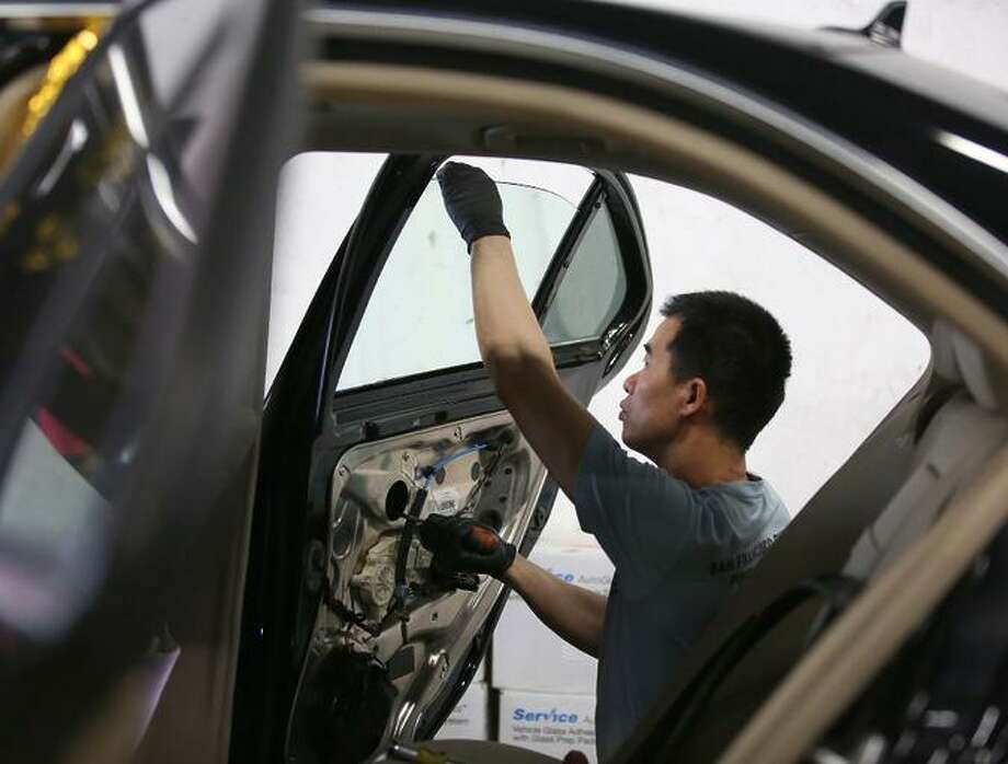 At TLC Auto Glass in San Francisco, Jimmy Lee replaces a car's window in August after a break-in. Photo: Liz Hafalia / The Chronicle 2017 / Liz Hafalia / The Chronicle 2017