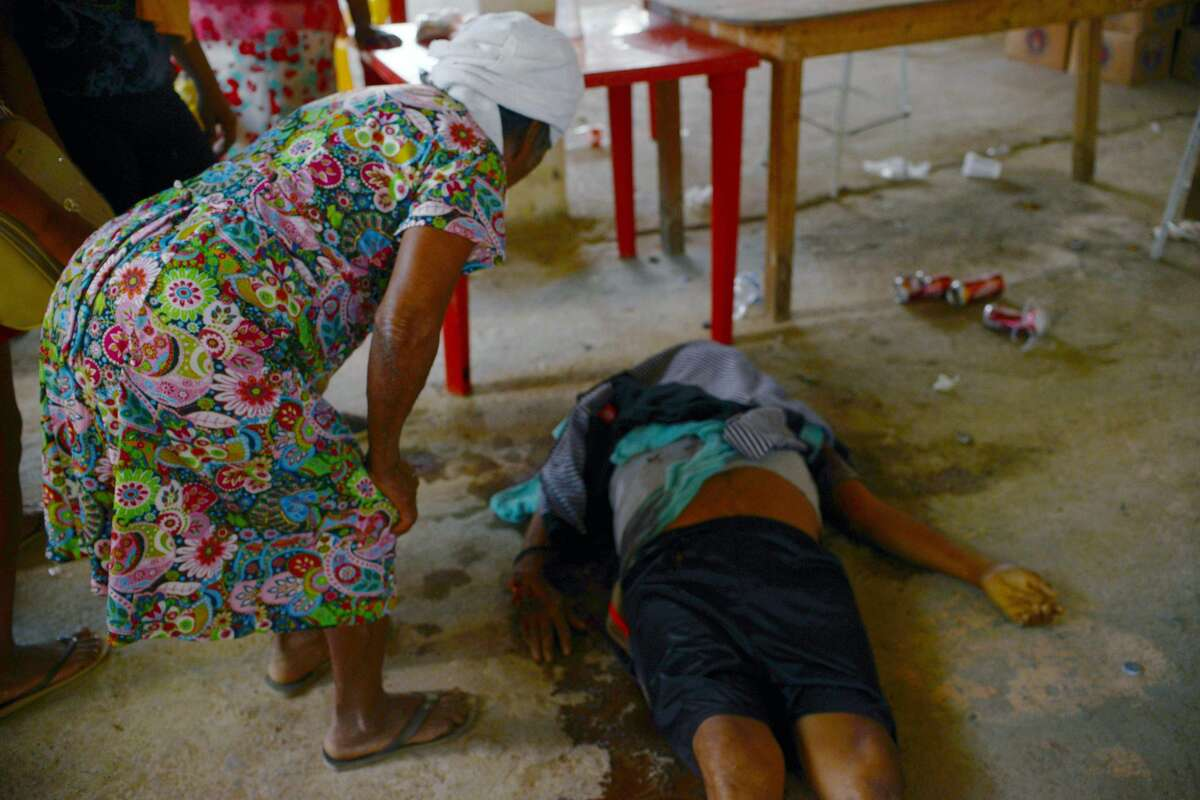 EDITORS NOTE: Graphic content / A woman looks at a corpse after a shooting took place at La Concepcion village, in Acapulco municipality, Guerrero state, Mexico, on January 7, 2018. At least 11 people were killed and 30 arrested during armed clashes among civilians, community guards and police in a rural area of Acapulco, in southern Mexico, the Guerrero government confirmed. / AFP PHOTO / FRANCISCO ROBLES (Photo credit should read FRANCISCO ROBLES/AFP/Getty Images)