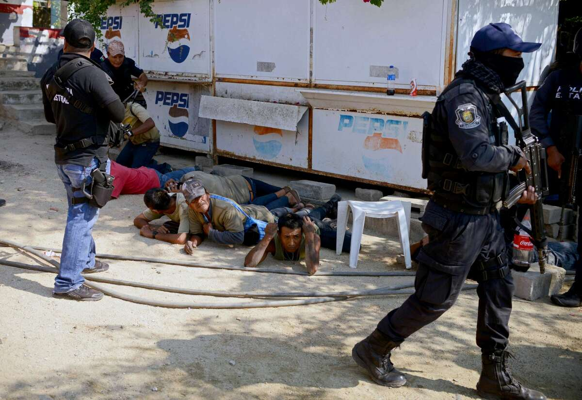Guerrero policemen are seen during the arrest of a member of the Regional Coordinator of Community Authorities (CRAC) after a series of clashes that left at least 11 people dead at La Concepcion village, Acapulco municipality, in Guerrero state, Mexico, on January 7, 2018. At least 11 people were killed and 30 arrested during armed clashes among civilians, community guards and police in a rural area of Acapulco, in southern Mexico, the Guerrero government confirmed. / AFP PHOTO / FRANCISCO ROBLES (Photo credit should read FRANCISCO ROBLES/AFP/Getty Images)
