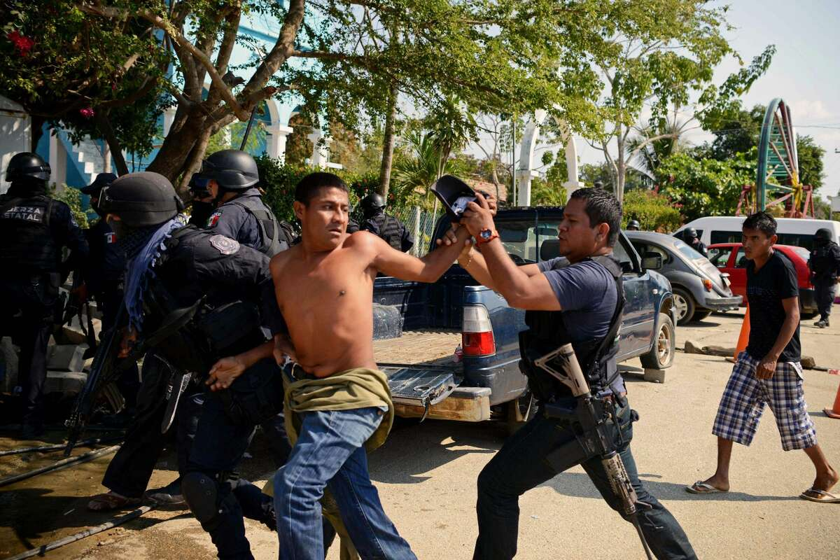 A member of the Regional Coordinator of Community Authorities (CRAC) is arrested by Guerrero state policemen after a series of clashes that has left at least 11 people dead at La Concepcion village, Acapulco municipality, in Guerrero state, Mexico, on January 7, 2018. At least 11 people were killed and 30 arrested during armed clashes among civilians, community guards and police in a rural area of Acapulco, in southern Mexico, the Guerrero government confirmed. / AFP PHOTO / FRANCISCO ROBLES (Photo credit should read FRANCISCO ROBLES/AFP/Getty Images)