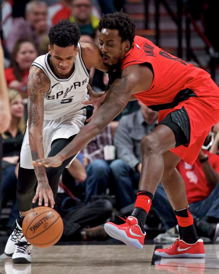 San Antonio Spurs guard Dejounte Murray, left, keeps the ball away from Portland Trail Blazers forward Al-Farouq Aminu during the first half of an NBA basketball game in Portland, Ore., Sunday, Jan. 7, 2018. (AP Photo/Craig Mitchelldyer) Photo: Craig Mitchelldyer, Associated Press / FR170751 AP